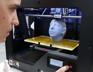 Manuel Leute poses for the media as he uses the 3D printer MakerBot Replicator 2 at the CeBit computer fair in Hanover